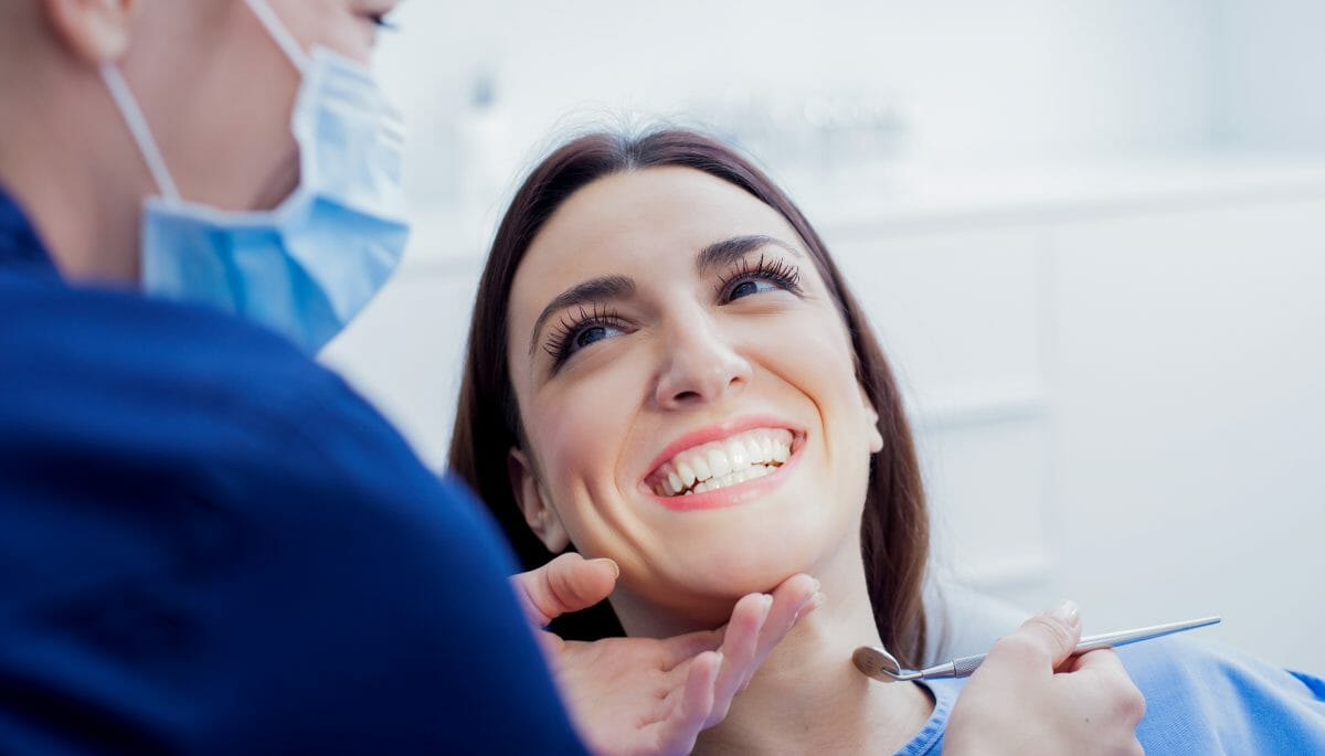 Dentist working on smiling patient with mirror in hand